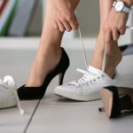 Eine Frau wechselt auf der Arbeit die Schuhe, von Pumps zu Freizeitschuhen