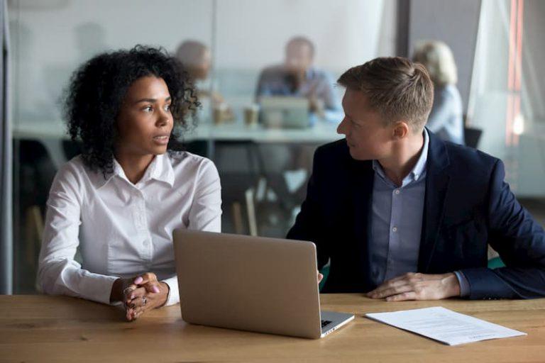 Ein Mann und eine Frau sitzen an einem Laptop