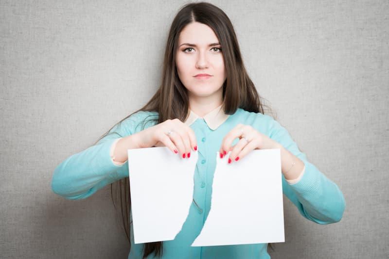 Eine Frau zerreißt ein Papier