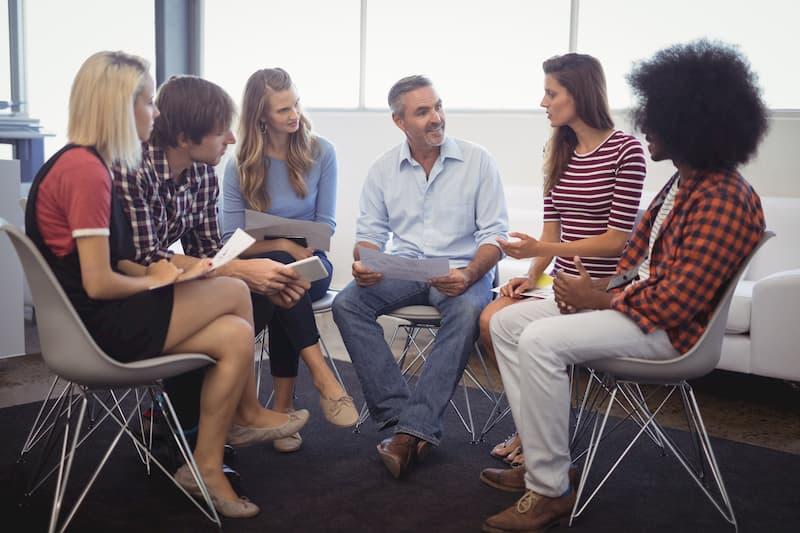 Sechs Menschen sitzen zusammen im Stuhlkreis