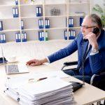 Ein alter Mann im Rollstuhl sitzt am Schreibtisch