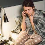 Eine Frau sitzt auf der Bettkante und telefoniert