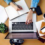 Eine Frau tippt auf dem Laptop und hält einen Stift