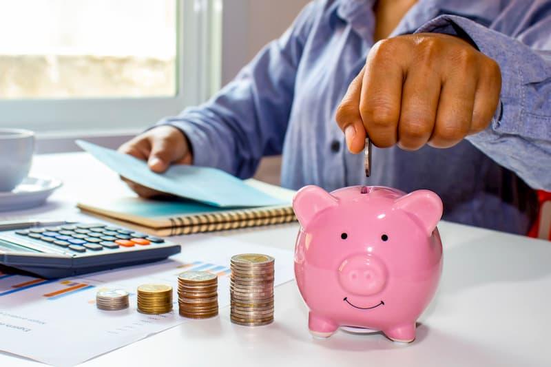 Eine Münze wird von einer Frau in ein Sparschwein geworfen