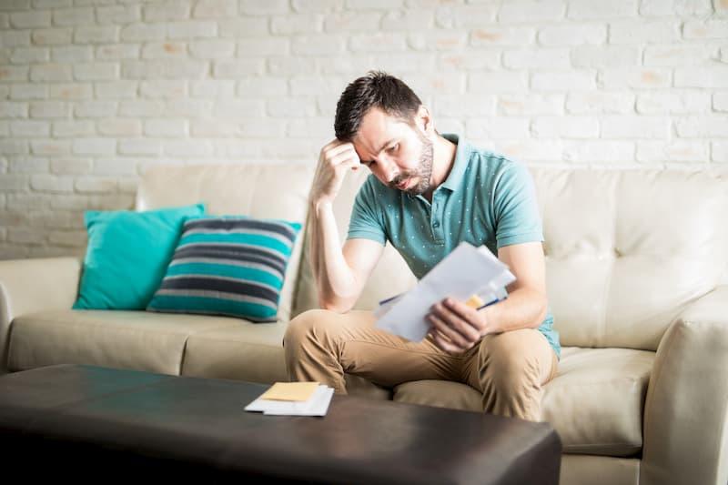 Ein Mann hat einen Brief in der Hand und ist besorgt
