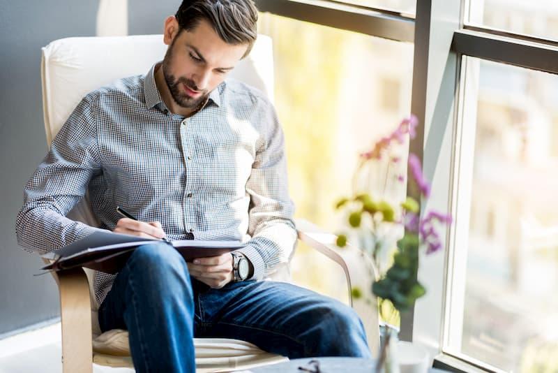 Ein Mann sitzt und schreibt an einem Text