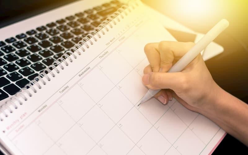 Ein Mensch schreibt auf seinem Arbeitsplan