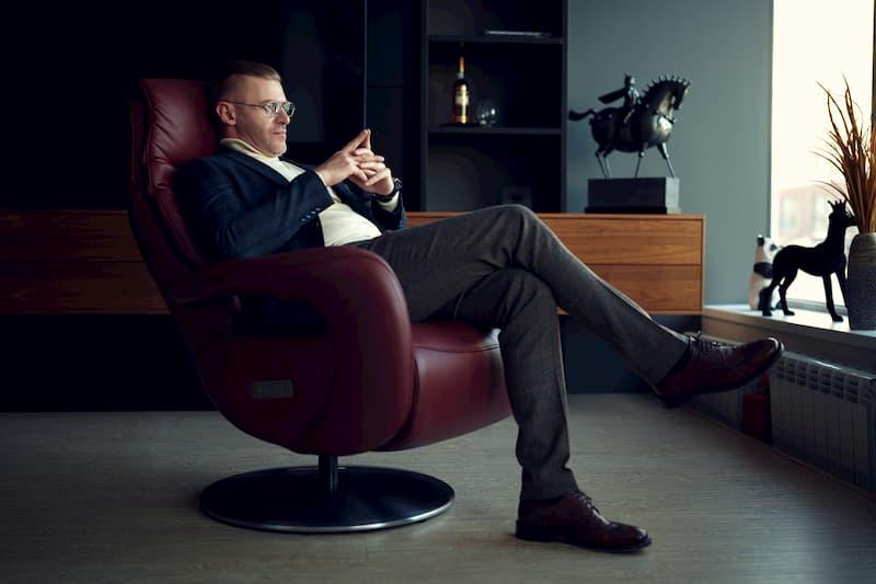 Ein Mann sitzt im Ledersessel und blickt in die Ferne