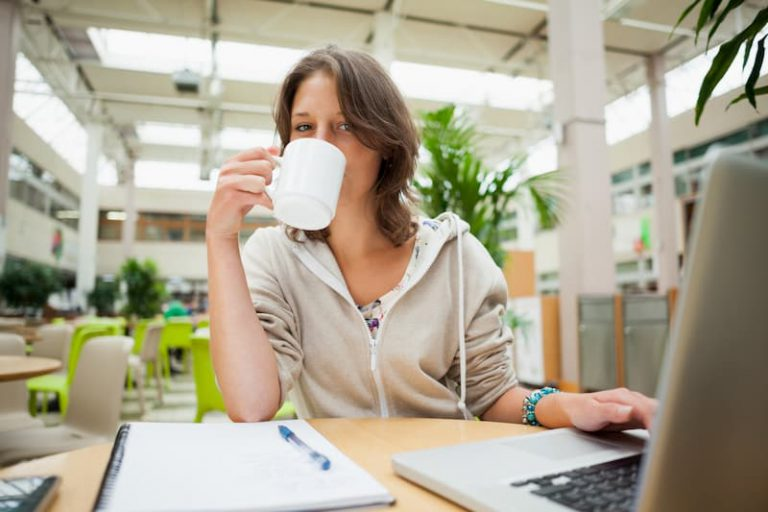 Eine Studentin sitzt im Cafe und macht eine Steuererklärung