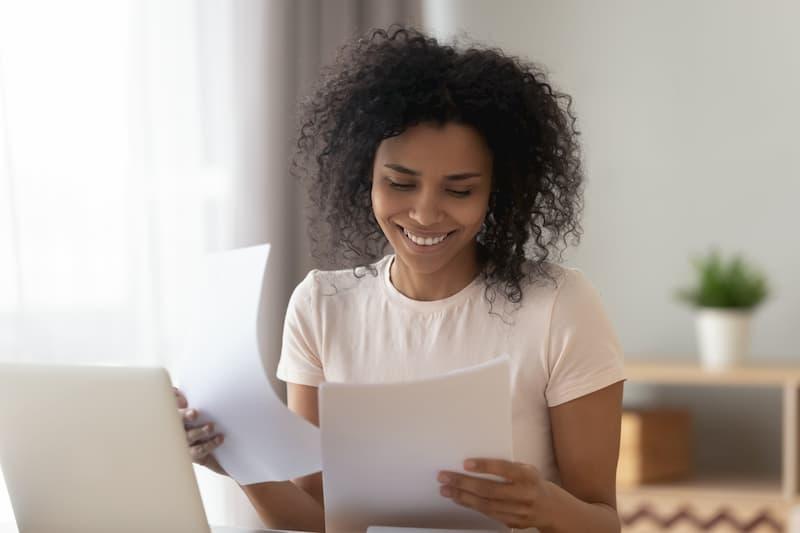 Eine Frau lächelt über ihr qualifiziertes Arbeitszeugnis in der Hand