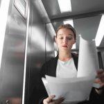 Eine Frau sieht in ihrem Arbeitsvertrag nach, ob es eine Kündigungsfrist gibt