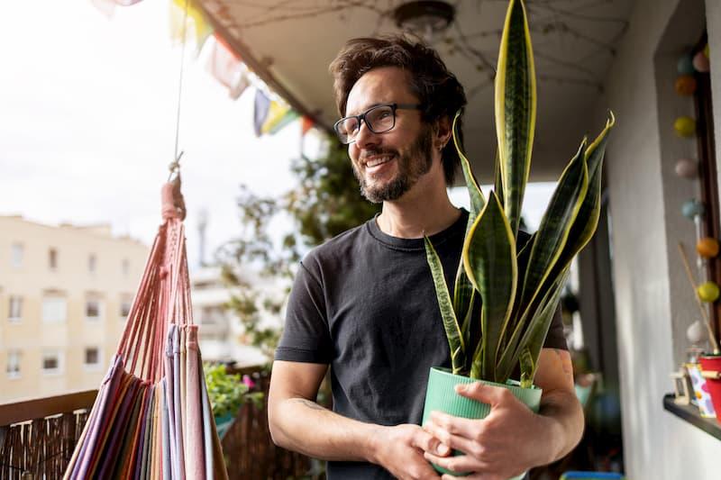 Ein Mann ist auf dem Balkon und kann sich während der Kurzarbeit um seine Pflanzen kümmern