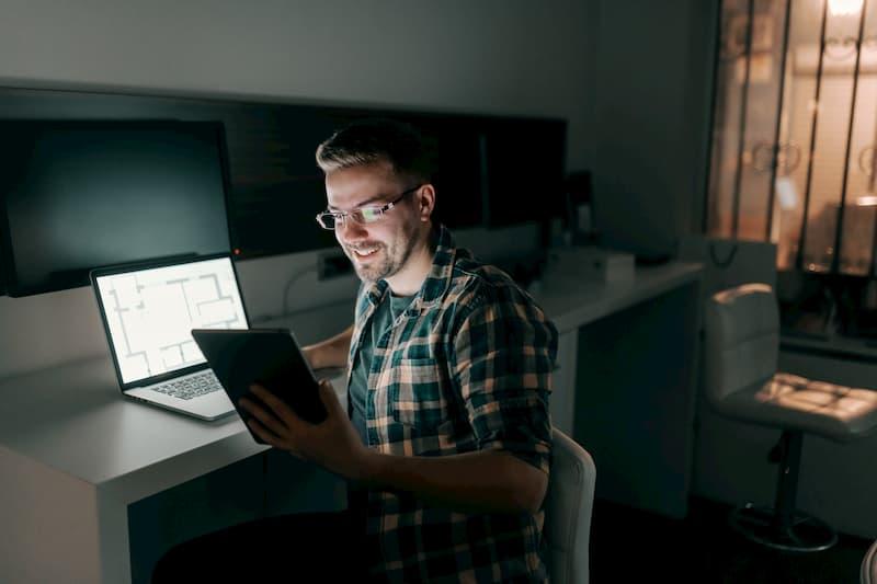 Ein Mann sitzt abends im Büro und ist zufrieden da er nach Vertrauensarbeitszeit arbeiten kann
