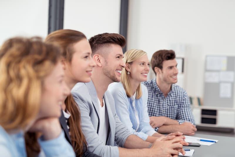 Mehrere Frauen und Männer sitzen am Tisch im Assessment Center