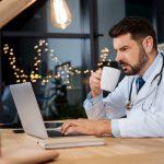 Ein Arzt sitzt in der Nacht am PC und macht Bereitschaftsdienst