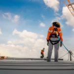 Ein Bauarbeiter steht auf einem Dachgerüst und ist geschützt, dank der Berufsgenossenschaft