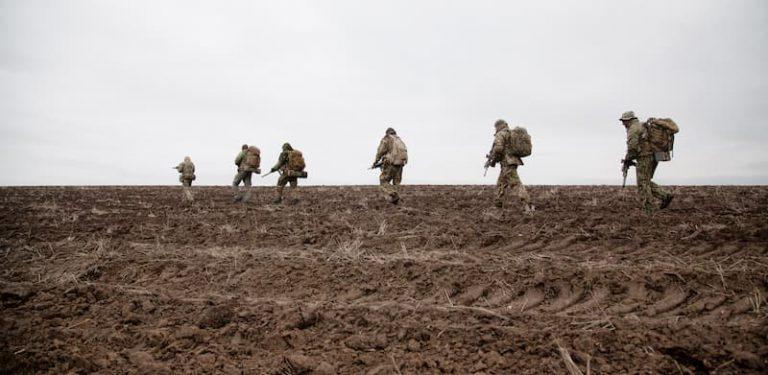 Mehrere Soldaten der Bundeswehr beim Marsch durch den Schlamm