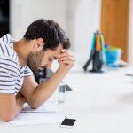 Ein Mann schaut Zuhause in seinen Arbeitsvertrag nach, ob es Vertragsstrafen gibt