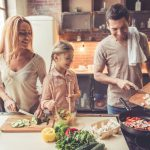 Bei einer 4-Tage-Woche bleibt mehr Zeit für die Familie, ein Mann kocht mit Frau und Kind