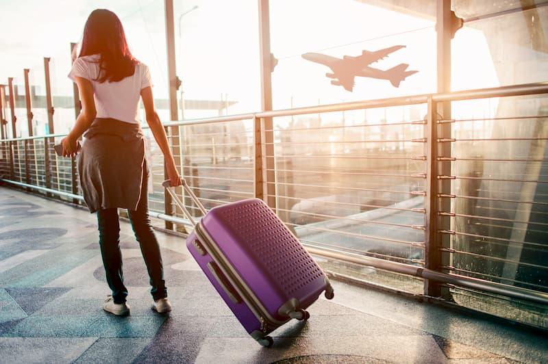 Eine Frau ist mit dem Koffer am Flughafen