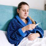 Eine Frau liegt krank im Bett, sie ist arbeitsunfähig