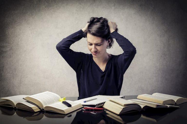 Eine Frau rauft sich die Haare, da es viele Tipps in Bewerbungsratgebern gibt.