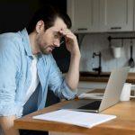Ein junger Mann sitzt vor dem Laptop und denkt über das Schreiben einer Kündigung nach