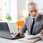 Ein Chef eines Unternehmens sitzt am Schreibtisch und sieht in die Verträge, da er eine Änderungskündigung durchführen möchte