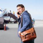 Ein Mann telefoniert am Flughafen vor dem Beginn seiner Dienstreise