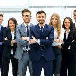 Mehrere Mitarbeiter stehen in einem Raum und sind glücklich, da sie eine Gewinnbeteiligung haben