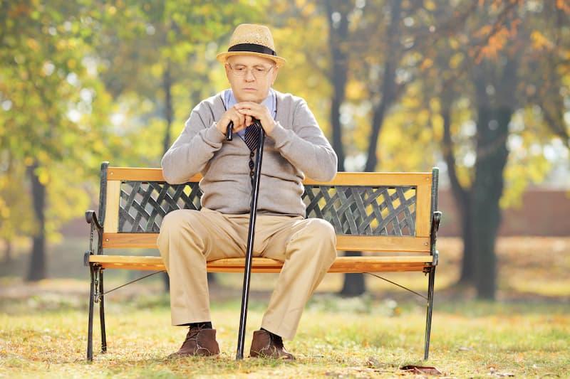 Ein alter Mann sitzt auf einer Parkbank und denkt über Grundsicherung nach