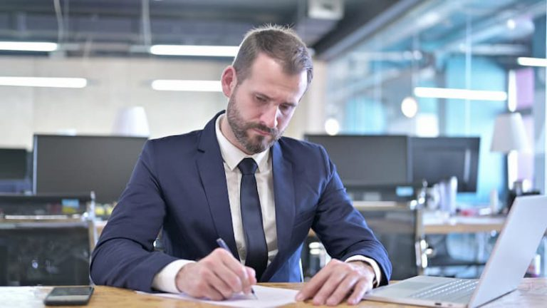 Ein skeptischer Arbeitnehmer unterschreibt einen befristeten Arbeitsvertrag