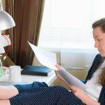 Eine Frau sitzt Zuhause und erhält eine krankheitsbedingte Kündigung