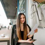 Eine Frau lächelt, da sie einen Ausbildungsvertrag in der Hand hält
