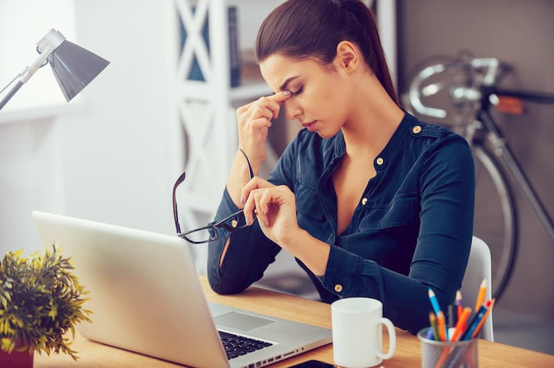 EIne Frau ist müde am Arbeitsplatz, eine Reaktion auf Stress