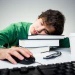 Ein Mann leidet an Boreout und ist übermüdet auf der Arbeit, deswegen schläft er auf Büchern