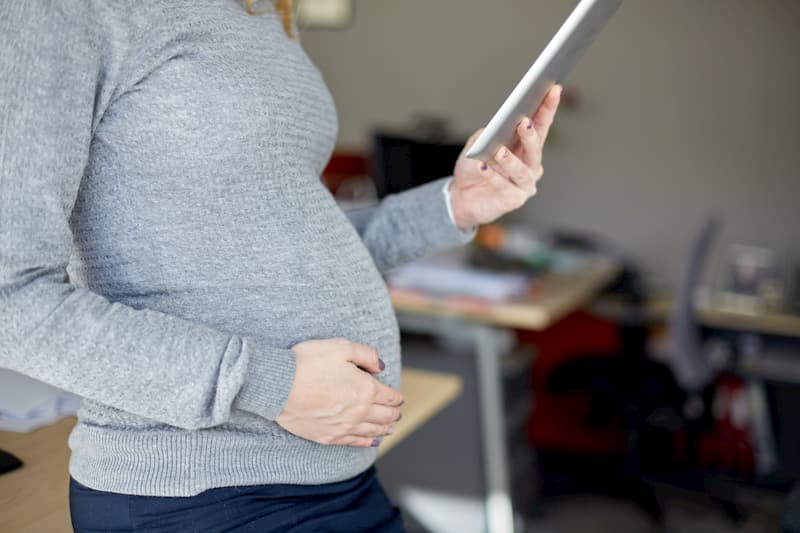 Eine schwangere Frau auf der Arbeit kurz vor dem Mutterschutz
