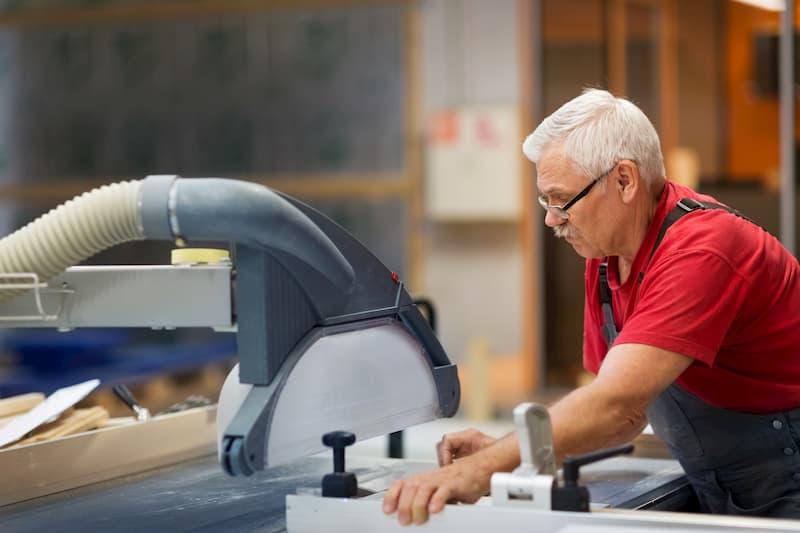 Ein älterer Arbeiter an einer Maschine in Altersteilzeit