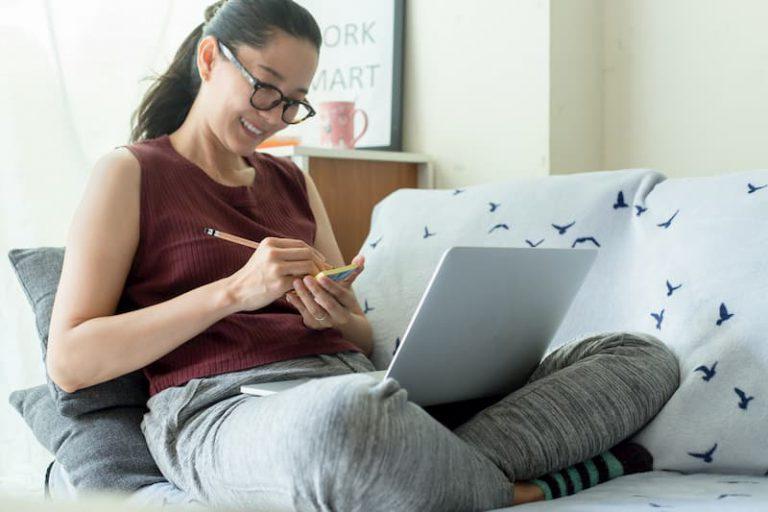 Eine Frau sitzt auf dem Sofa und arbeitet im Homeoffice mit Laptop auf dem Schoß