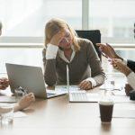Eine Geschäftsfrau ist im Meeting und leidet unter Burnout