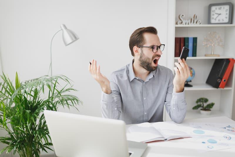 Ein Mann nutzt sein Handy am Arbeitsplatz, dies kann zu den Kündigungsgründen gehören