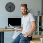 Ein junger Mann hält ein einfaches Arbeitszeugnis in der Hand