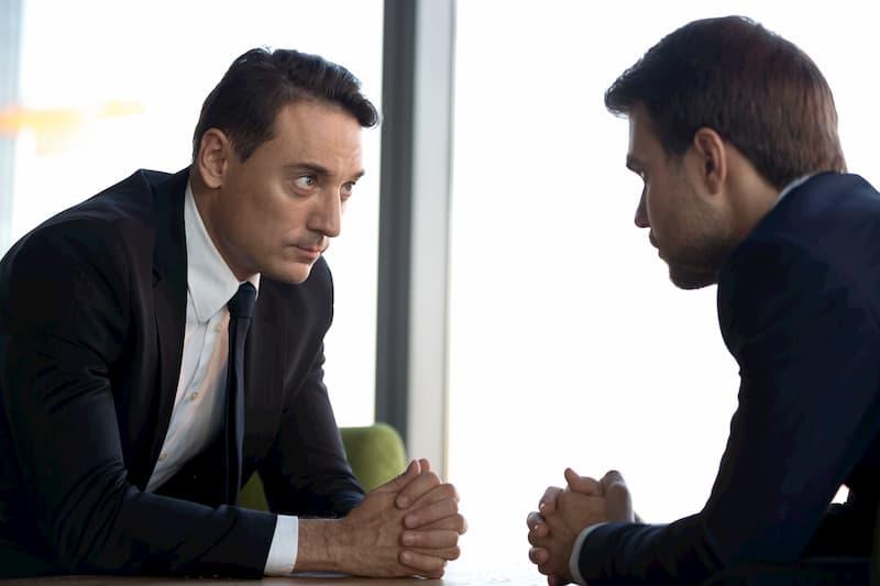 Ein Mann sitzt gegenüber vom Chef bei der Gehaltsverhandlung