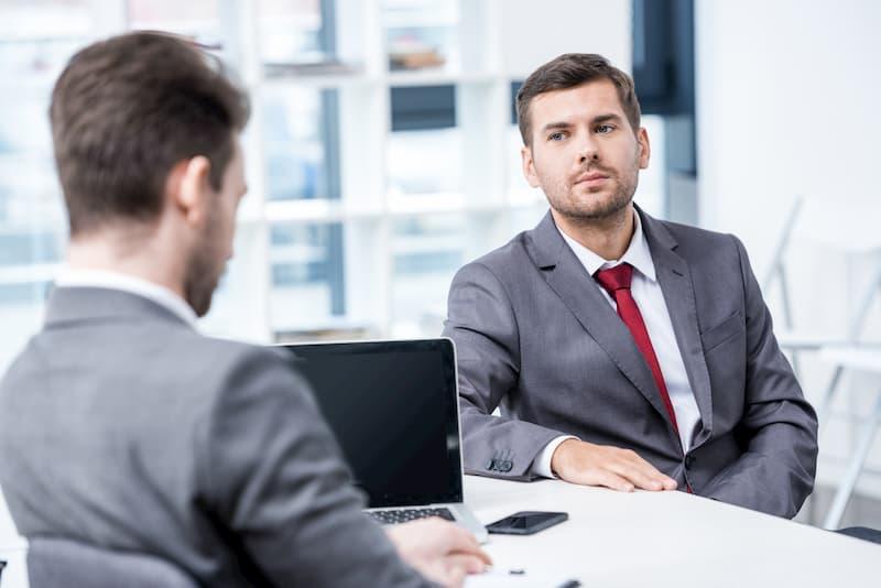 Ein Mann verhandelt im Gespräch mit dem Chef sein Einstiegsgehalt