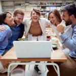 Mehrere Mitarbeiter sitzen vor dem Laptop und umarmen sich, es herrscht ein gutes Betriebsklima