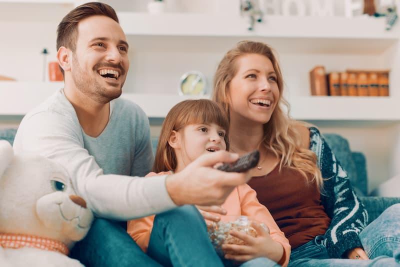 Zwei Eltern mit ihrem Kind auf dem Sofa, sie gehören in eine eigene Steuerklasse