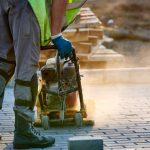 Ein Bauarbeiter nutzt einen Rüttler, der Lärm kann zu einer Berufskrankheit führen