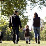Eltern machen mit Kind und Hund einen Spaziergang, sie sind entspannt aufgrund des Elterngeldes
