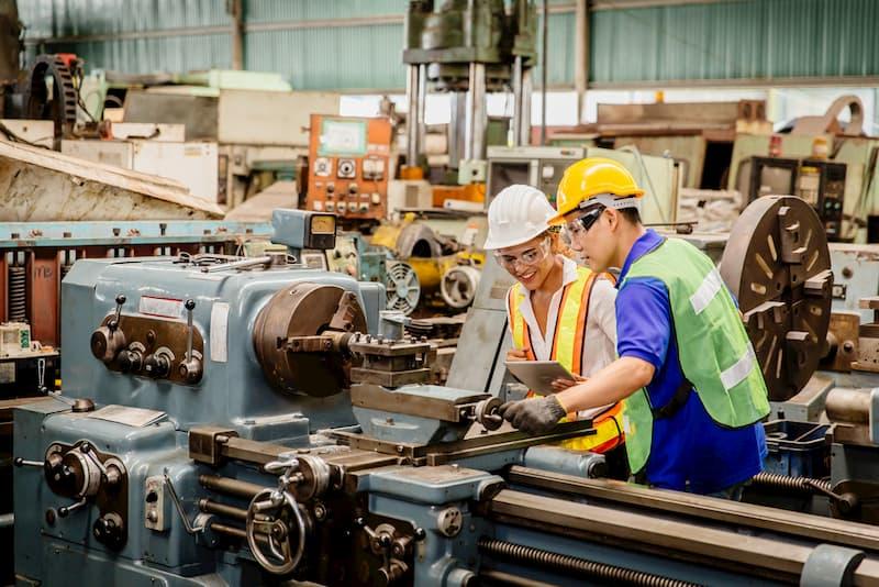 Eine Industriearbeiterin bekommt Hilfe vom Kollegen bei der Wiedereingliederung in den Job