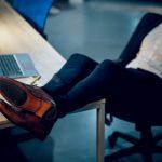 Ein Mann legt bei der Arbeit die Füße auf den Tisch, eine mögliche Form von Arbeitsverweigerung